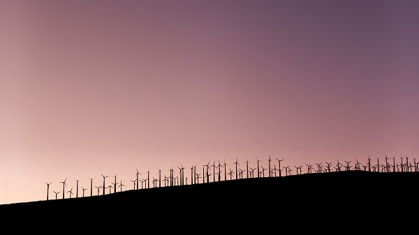 line of windmills on a hill sunset